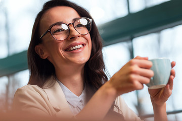 Great time. Low angle of cute nice joyful woman laughing on the blurred background while putting on glasses and enjoying coffee