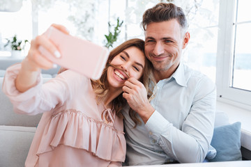 Photo of young and beautiful couple making selfie and having fun together, while having date in restaurant