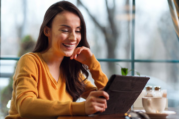 Way of work. Happy cheerful nice woman looking at screen while smiling and using tablet