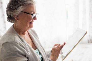 Smiling senior woman using digital tablet at home
