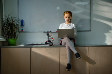 little schoolgirl using laptop on table at classroom with diy robot