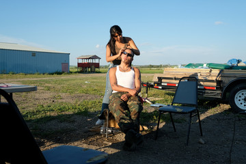 Trey Delaronde (Front), a member of the First Nation Indigenous Warriors, has his hair braided by his girlfriend, Bethany Jenelle, a member of the American Indian Movement, on the Cote First Nation, near the town of Kamsack, Saskatchewan