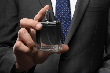Handsome man in formal suit and with bottle of perfume, closeup