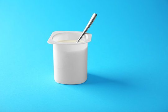 Plastic cup with yummy yogurt on color background