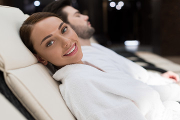 happy young woman smiling at camera while resting in spa center