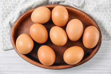 Plate with chicken eggs on light table