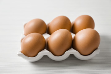 Holder with chicken eggs on light table