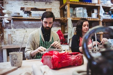 Female potter with male colleague working at table