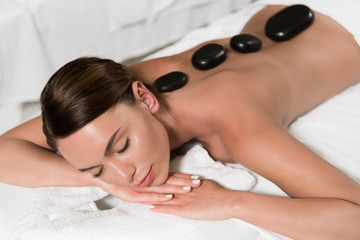 beautiful young woman having hot stones massage in spa salon