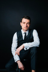 Color portrait of a young man in a white shirt and black tie, bored, looking to the side, against plain studio background.