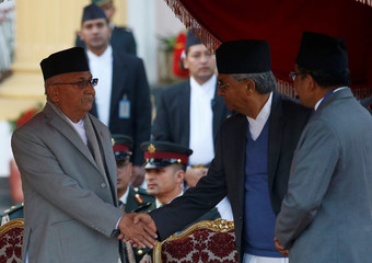 "Newly elected Nepalese Prime Minister Khadga Prasad Sharma Oli, also known as K.P. Oli, shakes hand with the outgoing Prime Minister Sher Bahadur Deuba, after administrating the oath of office at the presidential building ""Shital Niwas"" in Kathmandu"