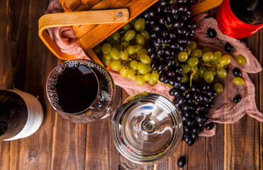 Photo on top of wine glasses, grapes of green and black, wooden basket, cloth