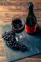 Photo of bottle of red wine, wine glass with wine, black grapes on stone board