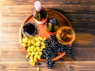 Picture on top of wine glass with wine, grapes black, green on wooden tray on table