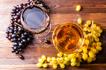 Image of two glasses with juice, grape, on wooden table,