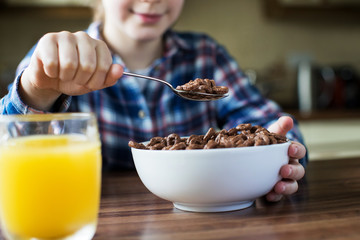Close Up Of Girl Eating Bowl Of Sugary Breakfast Cereal In Kitchen