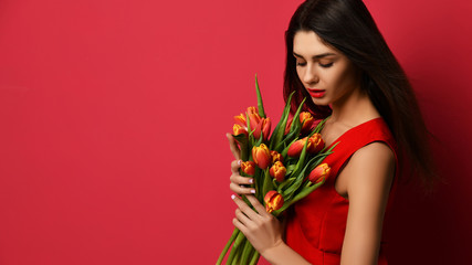 Beautiful woman with bouquet of tulip flowers in red dress and looking at the corner with empty text copy space