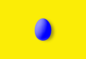 One blue isolated egg on a yellow background