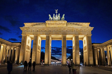 Sightseeing in Berlin. The Brandenburg Gate is illuminated by lights under a black sky in the center of Berlin.