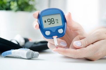 Woman checking blood sugar level by glucometer