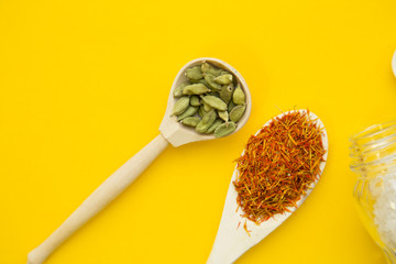 Plastic spoons with dry spices and fresh herbs on a yellow background with copy space, top view, close up