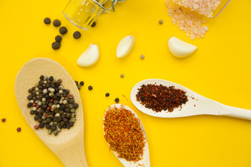 Wooden and plastic spoons with dry spices and fresh herbs on a yellow background with copy space, top view, close up
