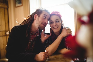 Hipster couple listening to music on smartphone