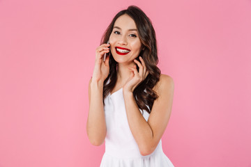 Studio portrait of young asian woman smiling with white teeth and talking on smartphone, isolated over pink background