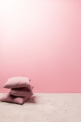 pillows on carpet in front of pink wall