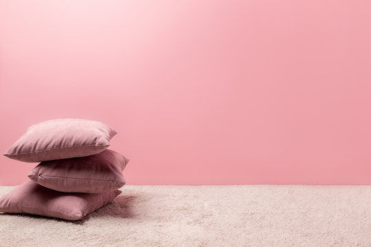 stack of pillows on carpet in front of pink wall