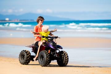 Kids on quad bike. Off road all terrain vehicle.
