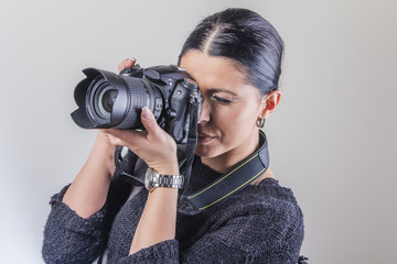 Cute young woman holding a dslr camera, professional photographer, studio image