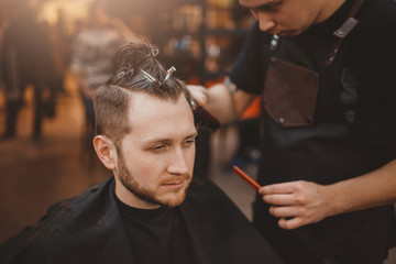 Barber shop. Customer man smiles and laughs during haircuts in Barbershop