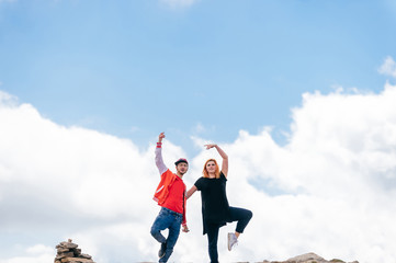 Couple of lovers dancing at top of mountain on massive clouds background. Happy pair in love celebrating success after reaching and conquering highest peak. Man and woman enjoying nature outdoor.
