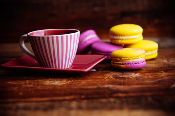colored macaroons and a Cup of coffee on a wooden table, color macaroons ultraviolet