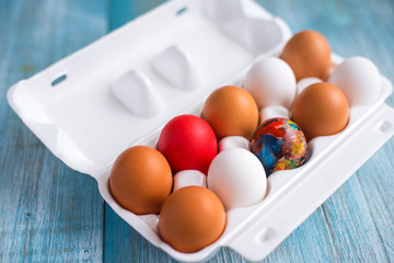 Chicken eggs in different colors in a box on a wooden blue surface