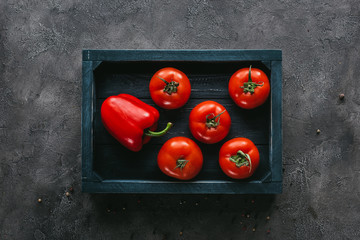 top view of tomatoes and bell pepper in box on concrete surface