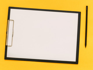 A blank paper on the balck tablet on yellow background. Flat lay, top view