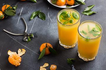 Tangerine juice in glasses on dark background