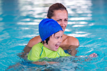 Little boy on swimming class with mother