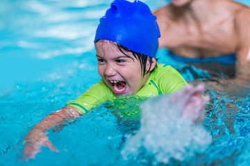 Excited little boy in a swimming pool