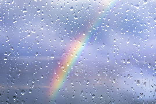 Rainbow through a window with drops after storm