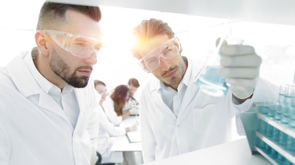 closeup. scientist and assistant studying the solution in the gl