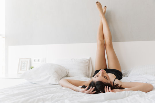 Portrait of a beautiful young woman lying on bed with legs up