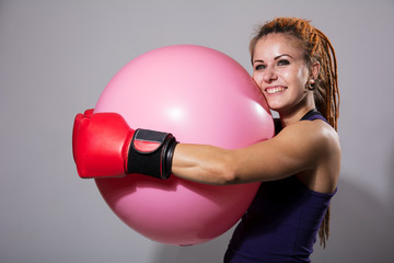 Young woman boxer with big rubber ball