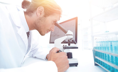 Young laboratory scientist looking at microscope in laboratory