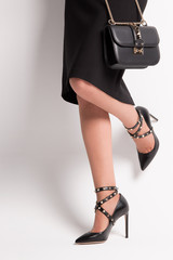 Accessories with fashion spikes. Accessories with fashionable thorns. Girl in shoes with a bag