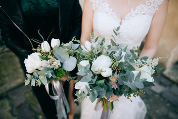 he bride and her friend hold hands in beautiful wedding bouquets of fresh flowers