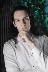 handsome manly guy with long black hair stands in white shirt on dark background