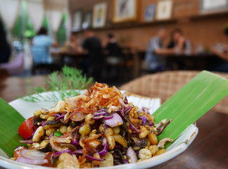Closeup of Burmese Tea Leaf Salad or Lahpet in a white plate with banana leaf on a dark wooden table with blurry restaurant background